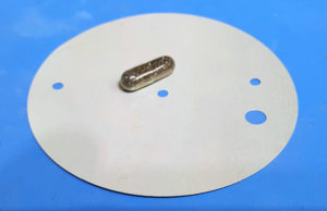 Metal diaphragm and capsule of carbon granules.